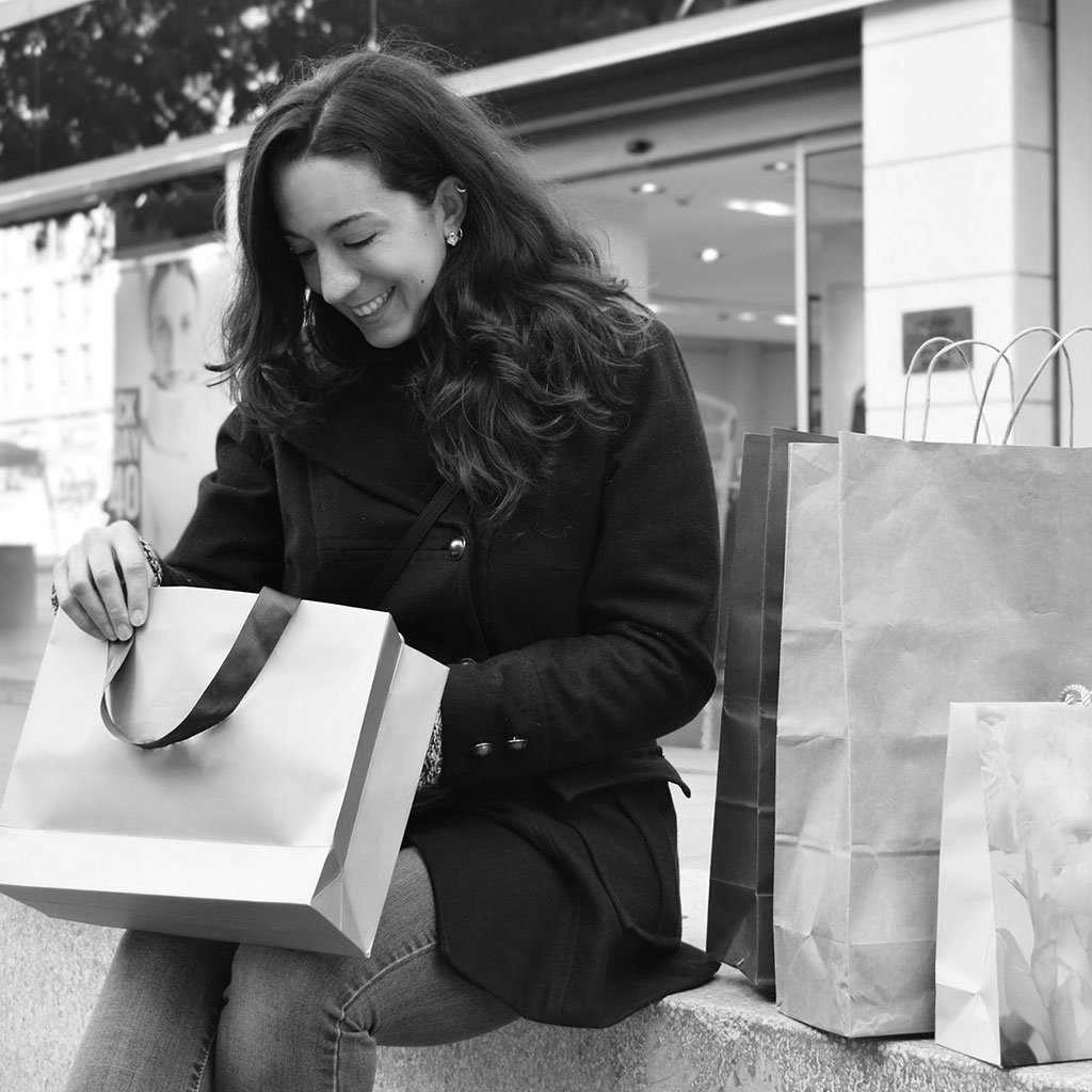 Woman-Looking-Into-Shopping-Bag-Smiling